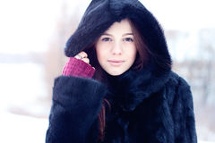 Beautiful brown-eyed brunette girl  winter  black coat posing  background trees, fashion style concept idea, portrait Stock Photography