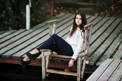 Beautiful brown-eyed brunette with long hair tousled by the wind, a white blouse, dark leggings and trendy shoes on. Beautiful brown-eyed brunette with long hair Stock Images