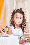 Beautiful brown-eyed girl drinking tea with sweets Royalty Free Stock Images