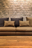 Beautiful brown fabric sofa on wooden floor with brick wall Stock Images