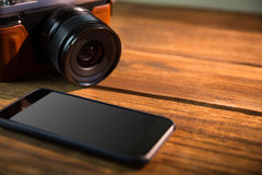 A beautiful brown fashioned camera next smartphone. On the wodden table Royalty Free Stock Images