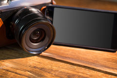 A beautiful brown fashioned camera next smartphone. On the wodden table Royalty Free Stock Image