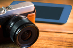 A beautiful brown fashioned camera next smartphone. On the wodden table Stock Photo