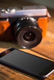 A beautiful brown fashioned camera next smartphone. On the wodden table Royalty Free Stock Photo