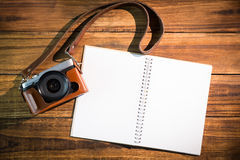 A beautiful brown fashioned camera next to notepad Stock Image