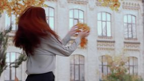 Beautiful brown hair lady holds yellow leaves in her hand and throws them stock footage