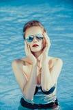 Beautiful brown hair woman near water wearing bikini. Royalty Free Stock Images