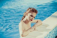 Beautiful brown hair woman near water wearing bikini. Royalty Free Stock Image