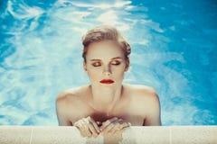 Beautiful brown hair woman near water wearing bikini. Royalty Free Stock Photos