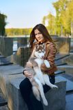 Beautiful brown haired girl holding a husky puppy in her arms stock images