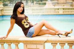 Beautiful brown haired girl by the pool Royalty Free Stock Photography