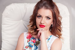 Beautiful Brown-haired model girl on white background . Hairstyle pigtail . Red lips and nails manicure Stock Photos