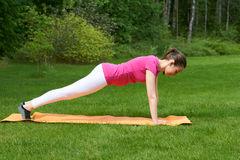 Beautiful brown haired woman doing exercises for muscles of hands, legs and stomach in plank pose on orange mat in nature. Royalty Free Stock Photos