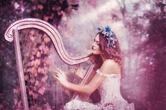 Beautiful brown-haired woman with a flower wreath on her head, wearing a white dress playing the harp in the forest. Royalty Free Stock Images