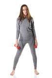 Beautiful brown haired woman wearing in sports gray thermal underwear standing with red dumbbells Royalty Free Stock Image