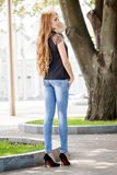Beautiful brown-haired young woman wearing clothes and walking o Stock Images