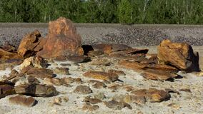 Beautiful brown stones of diferent size under the summer sun on quarry and green forest background. Stock footage. Rocks
