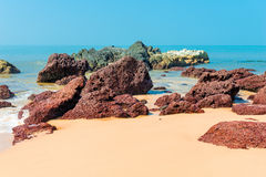 Beautiful brown stones, yellow sand and sea Royalty Free Stock Images
