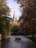 Beautiful Bruges. Canal view of Tourists in boat with Notre Dame in the background stock image