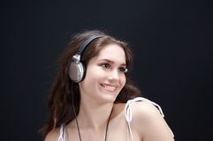 Beautiful brunette. On black background, listening music Stock Images