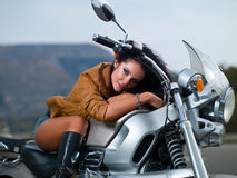 Beautiful brunette. Beautiful dark-haired girl on a motorcycle on the nature Stock Photography