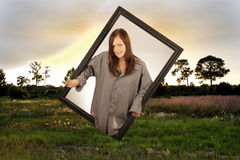 Beautiful Brunette in Another Dimension. A lovely young brunette appears to be emerging from a second dimension through a black, wooden picture frame into a royalty free stock photography