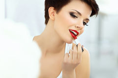 Beautiful Brunette applies lipstick.  Red Lips Royalty Free Stock Images