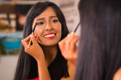 Beautiful brunette applying make up while smiling happily, seen from behind and face reflecting in mirror Stock Images