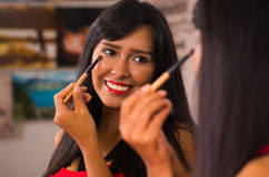 Beautiful brunette applying make up while smiling happily, seen from behind and face reflecting in mirror Royalty Free Stock Image
