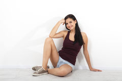 Beautiful brunette asian, caucasian fitness model sitting on floor near white wall in an empty room of the house. Royalty Free Stock Photography