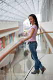 Beautiful brunette on a balcony. Portrait of a beautiful brunette on a balcony over a mall background Stock Photos