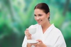 Beautiful brunette in bathrobe drinking herbal tea Royalty Free Stock Images