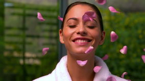 Beautiful brunette in bathrobe at the spa throwing up rose petals. In slow motion stock video footage