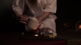 Beautiful brunette in bathrobe taking teapot and pooring tea in cup drinking herbal tea at the spa in slow motion. Thai. Tea ceremony. Slowmotion shot stock video