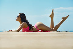 Beautiful brunette on the beach on a hot summer day Stock Photography