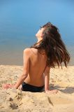 Beautiful brunette on  beach sunbathes topless Stock Image