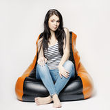 Beautiful brunette on bean bag. Beautiful brunette sitting on bean bag Royalty Free Stock Photos