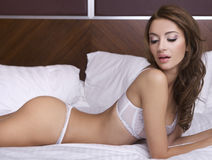Beautiful brunette in bed Stock Photos