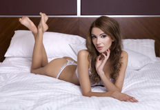 Beautiful brunette in bed Stock Images
