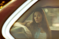 Beautiful brunette behind closed car window, tinted photo. Beautiful brunette with long hair behind closed car window, tinted photo Stock Images