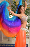 Beautiful brunette, belly dancer with rainbow shawl in the arabic harem interior. Beautiful belly dancer in the arabic harem interior with rainbow shawl Royalty Free Stock Photography