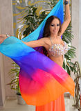 Beautiful brunette, belly dancer with rainbow shawl in the arabic harem interior. Beautiful belly dancer in the arabic harem interior with rainbow shawl Royalty Free Stock Photos