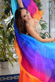 Beautiful brunette, belly dancer with rainbow shawl in the arabic harem interior. Beautiful belly dancer in the arabic harem interior with rainbow shawl Royalty Free Stock Images
