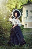 Beautiful brunette in a big black and white hat. White blouse and black skirt stock images