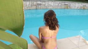 Beautiful brunette in bikini looking at camera stock video