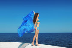 Beautiful brunette bikini model woman with blowing tissue over b. Lue sky, outdoors. Brunette girl at seaside. Summertime Royalty Free Stock Images