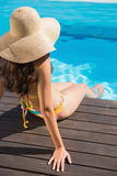 Beautiful brunette in bikini sitting by the pool paddling Stock Image
