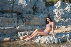 A beautiful brunette in a bikini is sitting on a stone. Sexy brunette girl in bikini posing on a beach.  stock image