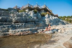 A beautiful brunette in a bikini is sitting on a stone. Sexy brunette girl in bikini posing on a beach.  royalty free stock images