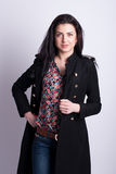 Beautiful brunette in a black coat. Stock Photography